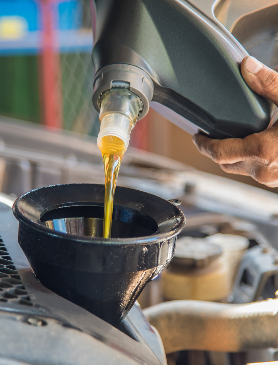 Mechanic pouring new oil into a car engine - Car Servicing Chard